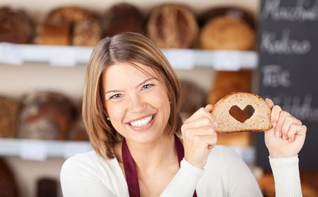 Brot-Verkäuferin in einer Bäckerei mit einem Stück Brot mit einem Loch in Herz-Form als Sinnbild für Kundenorientierung.