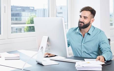 Büroangestellte mit einem A-Post-Brief in der Hand.