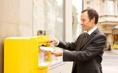 Ein Geschäftsmann steckt Briefe als B-Post-Einzelsendungen in einen Briefeinwurf.