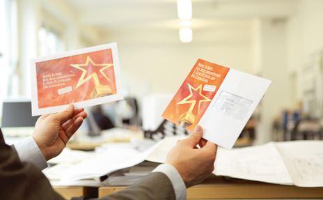 Ein Mann hält zwei speziell gestaltete Briefumschläge in der Hand.