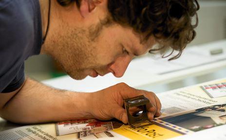 Probedrucke werden vor dem Gut zum Druck mit einer Lupe geprüft.