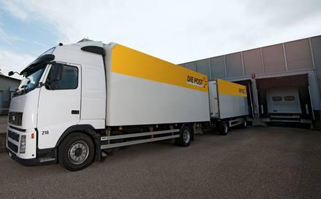 Ein Chauffeur der Schweizerischen Post belädt einen Transporter mit Stückgut.