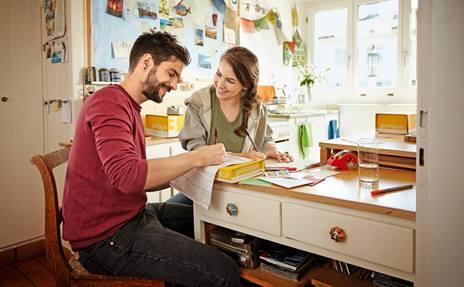 Una donna e un uomo siedono in cucina e indirizzano pacchi.