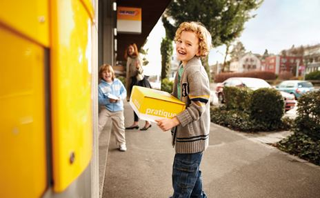 A boy stands in front of the post office with a yellow PostPac box and wants to post the parcel.
