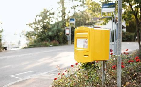 Une jeune femme assise sous un arbre dans le parc tient dans sa main une lettre d'amour envoyée par l'être aimé de l'autre bout de la Suisse